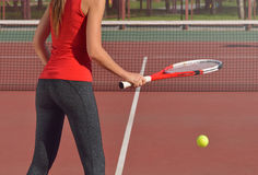 Young adult woman with racket ready to serve a tennis ball Stock Photography