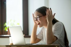 Young adult woman receiving good news via her laptop royalty free stock images