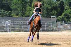 Young adult woman riding a bucking horse. During a barrel race Royalty Free Stock Photography