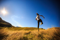 Young adult woman running on meadow Stock Photo