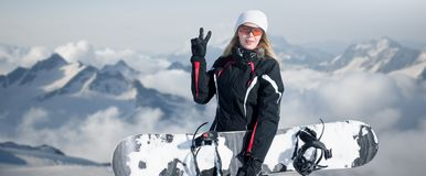 Young adult woman snowboarder holding board in hand in snow winter on the mountainside in fashion black sportswear smiles and royalty free stock photos