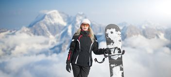 Young adult woman snowboarder holding board in hand in snow winter on the mountainside in fashion black sportswear smiles and royalty free stock photography