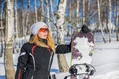Young adult woman snowboarder holding snow board. Young adult woman snowboarder holding board in heand in snow winter stock photos