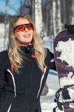Young adult woman snowboarder holding snow board. Young adult woman snowboarder holding board in heand in snow winter stock images