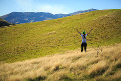 Young adult woman streching on meadow. At Lake Johnson, Queenstown, New Zealand Stock Images