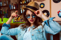 Young adult woman in sunglasses drink cocktail in bar Stock Photos