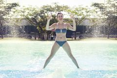 Young adult woman in swimsuit makes gymnastics. By the poolside Royalty Free Stock Image
