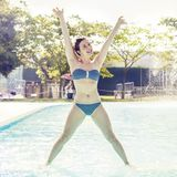 Young adult woman in swimsuit makes gymnastics. By the poolside Stock Images