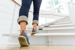 Young adult woman walking up the stairs. With sun sport background Royalty Free Stock Photography
