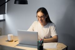 Young adult woman working on laptop computer late at night. Girl doing video chat job interview for position in remote town in evening at workplace desk in royalty free stock image