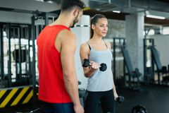 Young adult woman working out in gym with trainer Stock Photo
