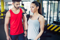 Young adult woman working out in gym with trainer. Young adult women working out in gym doing biceps with trainer Royalty Free Stock Photography