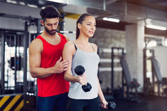 Young adult woman working out in gym with trainer. Young adult women working out in gym doing biceps with trainer Royalty Free Stock Images