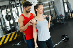 Young adult woman working out in gym with trainer. Young adult women working out in gym doing biceps with trainer Stock Images