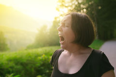 Young adult woman yawning outdoors in the morning Stock Photography