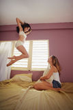 Young adult women jumping for joy on bed Stock Photo
