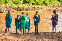 Young adults of the African tribe Suri, Omo Valley, Ethiopia. OMO VALLEY, ETHIOPIA - MAY 3, 2015 : Young adults of the African tribe Suri standing on the banks stock image