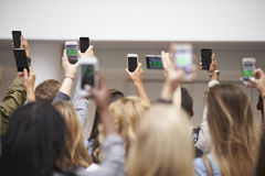 Young adults with arms raised take pictures with smartphones Stock Photos