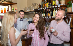 Young adults in bar. Cheerful young adults waiting for table and having beverages at bar Royalty Free Stock Photos