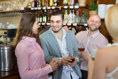 Young adults in bar. Group of happy smiling young adults chatting in bar with drinks. Focus on guy Stock Photos