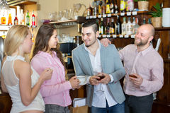 Young adults in bar. Group of happy smiling young adults hanging out in bar with beverages Royalty Free Stock Images