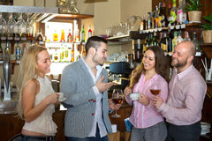 Young adults in bar. Group of positive smiling young adults hanging out in bar with drinks Royalty Free Stock Photos