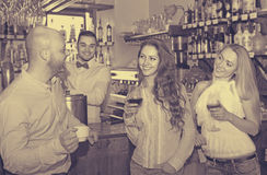 Young adults in bar. Happy young adults waiting for table and having beverages at bar. Selective focus Royalty Free Stock Image