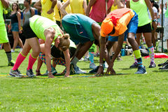 Young Adults Bend And Stretch Playing Grass Twister Royalty Free Stock Images