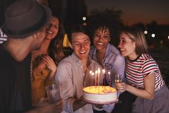Young adults celebrating with a birthday cake on a rooftop stock photo