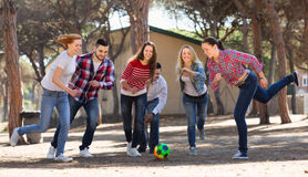 Young adults chasing ball outdoors Stock Photos