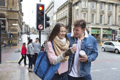 Young adults in the city. A young couple can be seen walking down a street looking at a smartphone together. Other young adults can be seen behind them Stock Photo