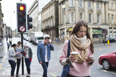 Young adults in the city. A young women can be seen walking along a city street with a smart phone. Other young adults are in the background using smart phones Stock Image