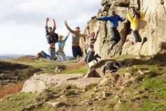 Young adults on country walk. And jumping in the air Royalty Free Stock Photos