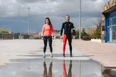 Young adults couple gets ready to run. In the street after rain Stock Images