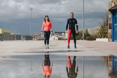 Young adults couple gets ready to run. In the street after rain Stock Photography