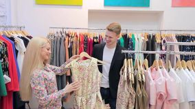 Young adults couple in good mood shopping at the clothing store stock footage