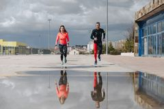 Young adults couple running together. In the street after rain Royalty Free Stock Photo