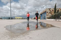 Young adults couple running together. In the street after rain Stock Images