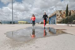 Young adults couple running together. In the street after rain Stock Photo