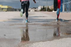 Young adults couple running together. In the street after rain Stock Photos