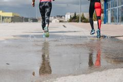 Young adults couple running together. In the street after rain Royalty Free Stock Photography