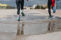Young adults couple running together. In the street after rain Royalty Free Stock Image