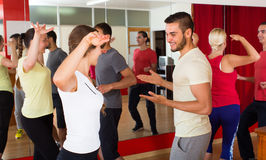 Young adults dancing in a studio. Cheerful young couples dancing active dance in studio. Selective focus Stock Images