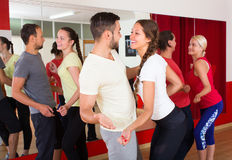 Young adults dancing in a studio. Cheerful young couples dancing in studio and smiling. Selective focus Royalty Free Stock Images