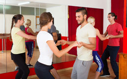 Young adults dancing in a studio. Cheerful couples dancing in studio and smiling. Selective focus Stock Images