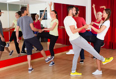 Young adults dancing in a studio. Cheerful energy young people having dance class. Selective focus Stock Photo