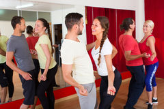 Young adults dancing in a studio. Cheerful young adults having dance class at studio. Selective focus Royalty Free Stock Images
