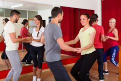Young adults dancing in a studio. Energy young couples dancing active dance in class. Selective focus Royalty Free Stock Photo
