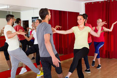 Young adults dancing in a studio. Group of cheerful adults dancing active dance in class. Selective focus Stock Photography