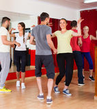 Young adults dancing in a studio. Happy young couples dancing active dance in studio. Selective focus Royalty Free Stock Image